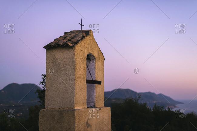 Little yellow chapel at sunset. Corfu island, Greece