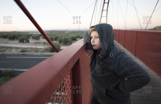 Young boy of 10 years with hoodie and sweatshirt looks out on pedestrian bridge to observe traffic and sunset in autumn night