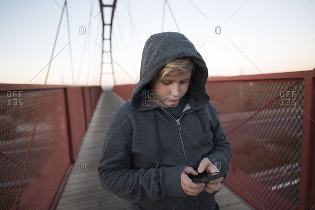 Young 10 year old boy with phone and hoodie on a bridge