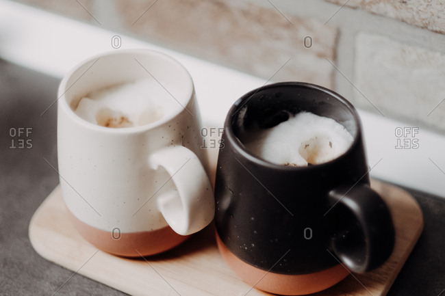 Close of up of coffee mugs with coffee and milk foam on wooden board