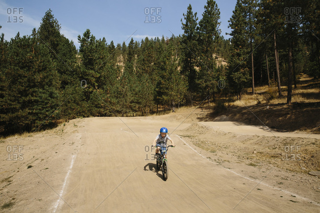 Boy rides dirt bike on a park course
