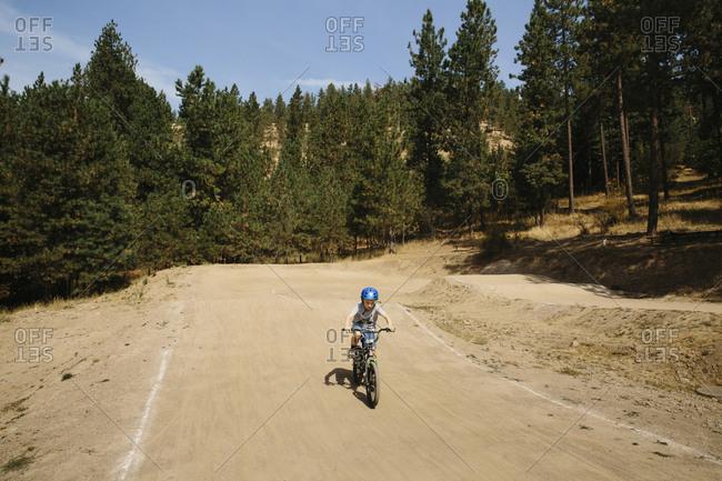 Boy rides dirt bike on a park course