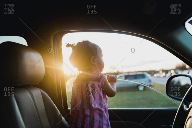Toddler girl looking out window of car