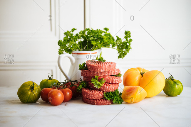 Raw meat patties stacked on counter with whole tomatoes
