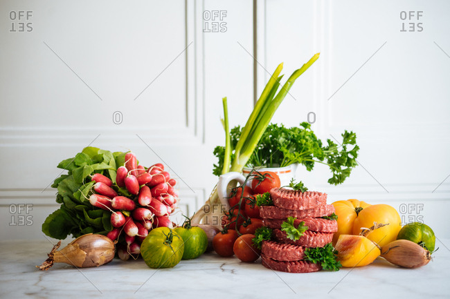 Raw meat patties and fresh vegetables