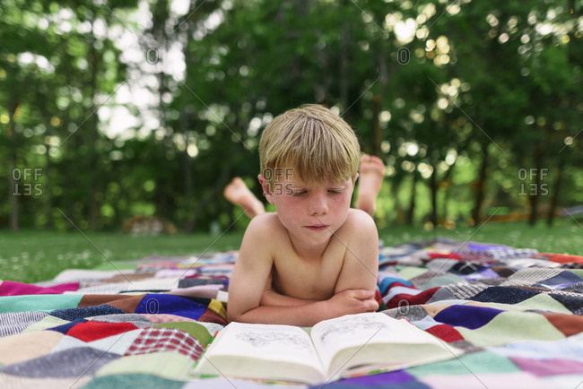 Young boy reading outside in the back yard