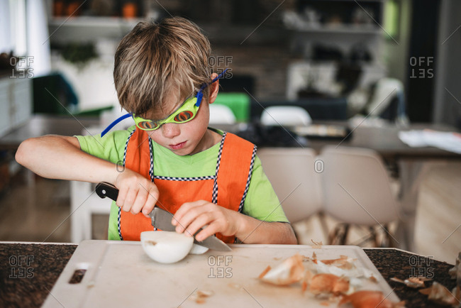 Young boy helping cutting onions in the kitchen
