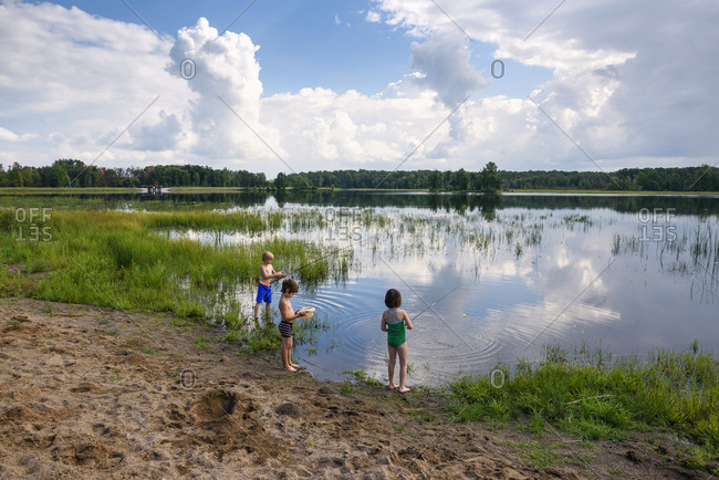 Young boys and girl fishing in peaceful lake with reflection of sky and clouds