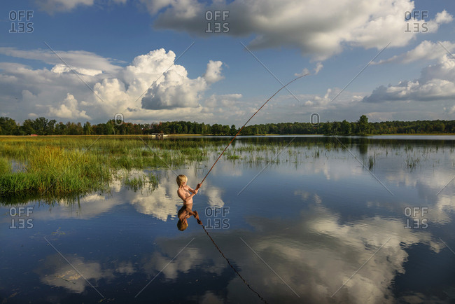 Young boy fishing in peaceful lake with reflection of sky and clouds