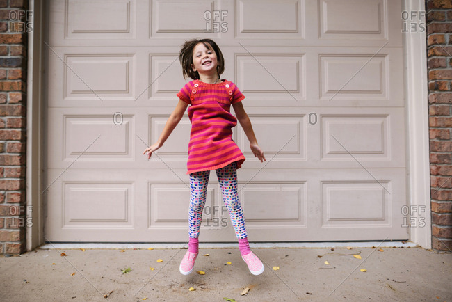 Young girl leaping in front of a wall
