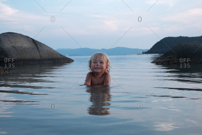 Portrait of cute blond little boy swimming in the sea and smiling at camera cheerfully