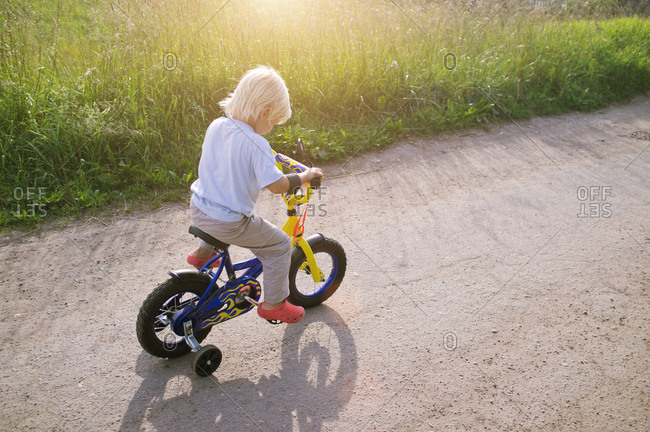 Happy childhood. Blond-haired little boy learning to ride his first bicycle with training wheels on rural road on beautiful summer day