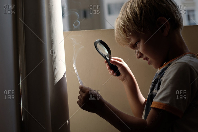 Curious blond-haired boy burning paper with magnifying glass