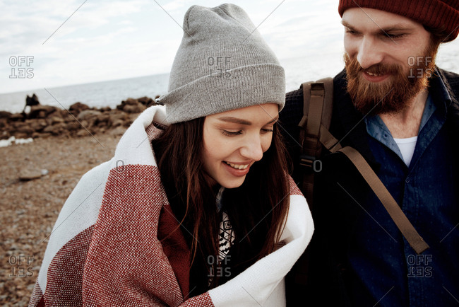 Portrait of young attractive brunette walking with handsome bearded man by the sea on cold autumn afternoon and smiling happily