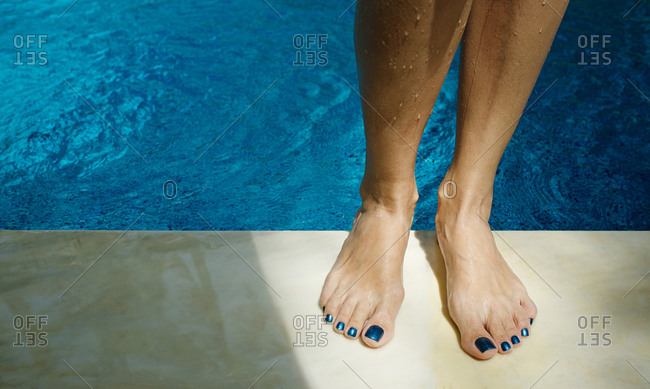 Unrecognizable woman with beautiful blue pedicure standing by swimming pool, her legs illuminated by sunlight