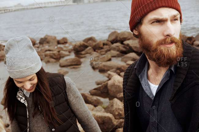 Portrait of young bearded man looking into the distance while walking along  rocky seacoast with beautiful dark-haired girl on cloudy autumn afternoon