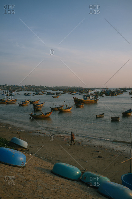 Panoramic view on traditional fishing boats in Mui Ne harbor, Phan Thiet city, Vietnam. Quiet water surface with small ripples, cloudless sky at sunset. Silhouette of local man walking along seashore and enjoying amazing view.