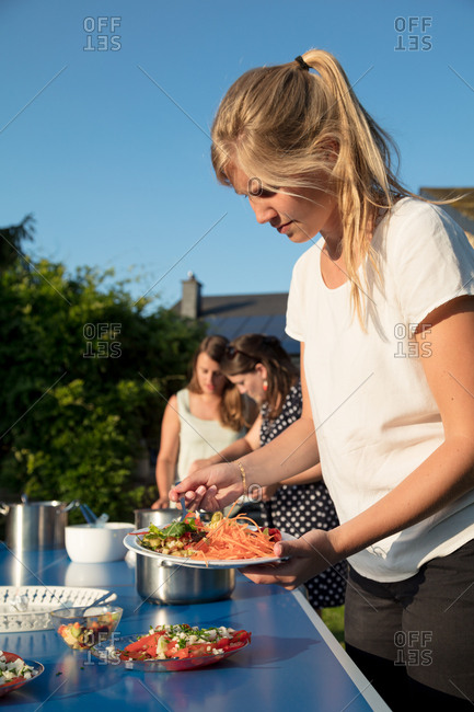 Woman fills her picnic plate with salads