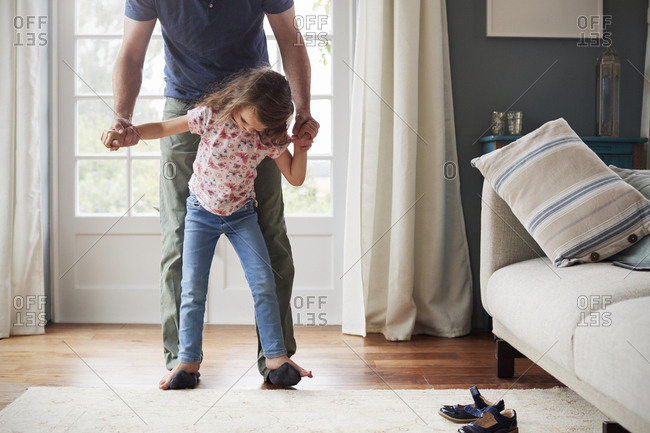 Girl balances walking on father�s feet at home, looking down
