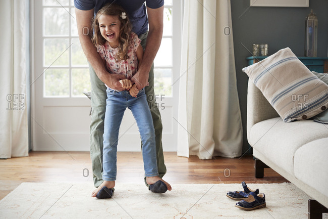 Girl balancing on father�s feet at home, looking to camera