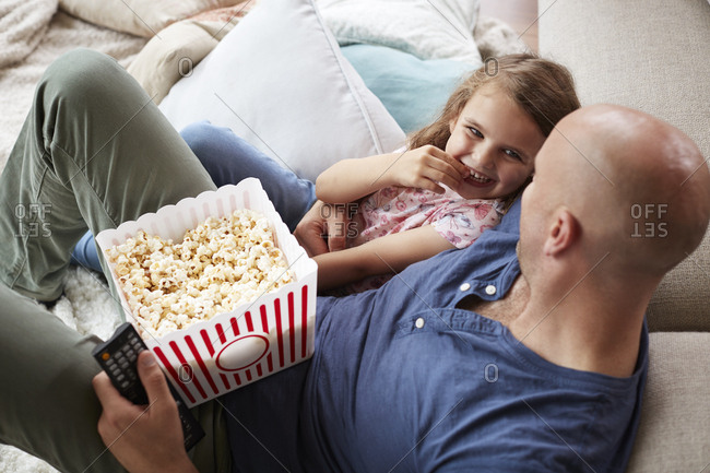 Dad and daughter eating popcorn at home, elevated side view