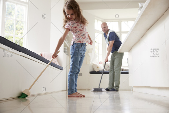 Dad and daughter sweeping the kitchen floor together