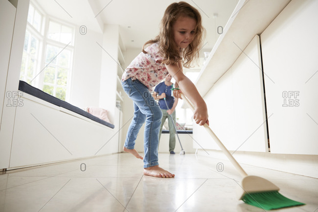 Young girl sweeping kitchen floor, dad in background