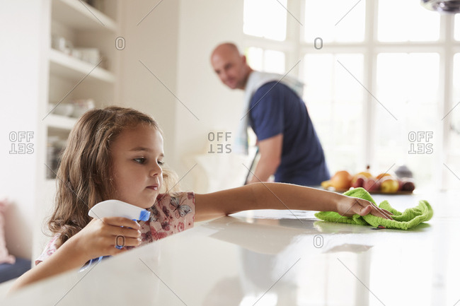 Young girl cleaning kitchen worktop, dad in background