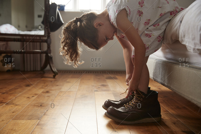 Young girl sitting on bed trying on dad's shoes