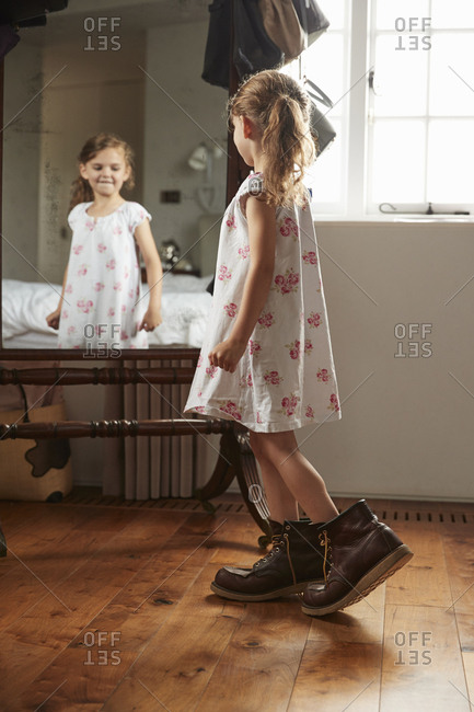Young girl wearing her dad�s boots looking in bedroom mirror