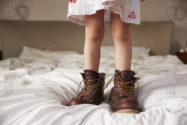 Young girl standing on bed wearing dad�s boots, low section