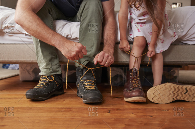 Dad teaching his daughter how to tie shoelaces, low section