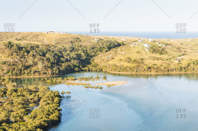 A landscape color image of Mdumbi River close to where it meets the sea. Villages and huts can be seen on the surrounding hills. Mdumbi, Eastern Cape of South Africa.