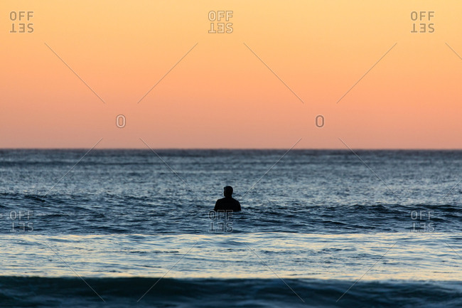 Surfer in wetsuit in the ocean waves at sunset