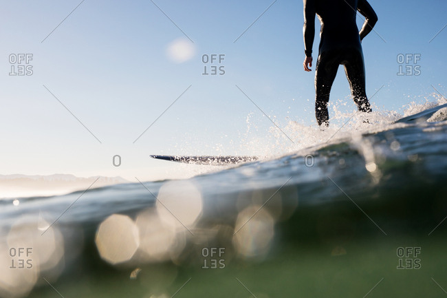 Surfer standing on board riding a wave