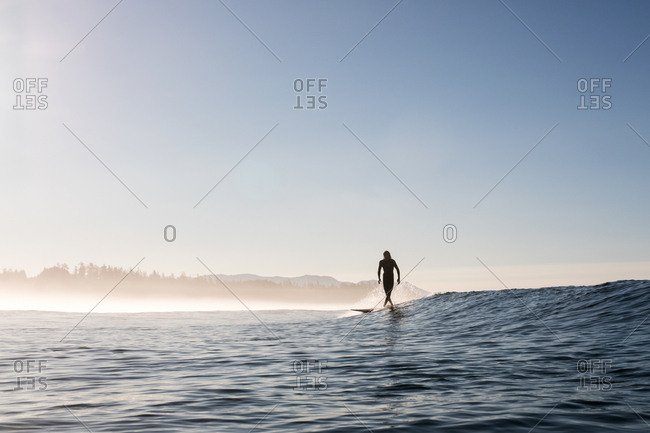 California, USA - September 3, 2017: Man riding surfboard on a small wave