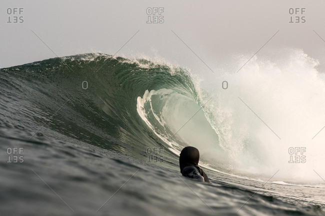 Surfer in wetsuit under a cresting wave