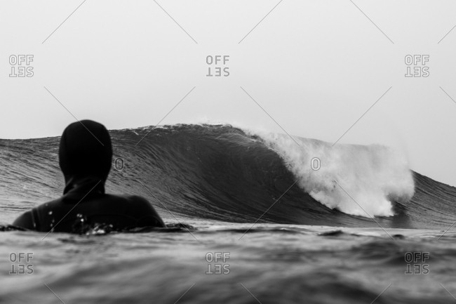 Surfer in wetsuit watching a cresting wave in black and white