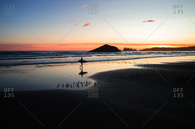 Surfer carrying board on a beach at sunset
