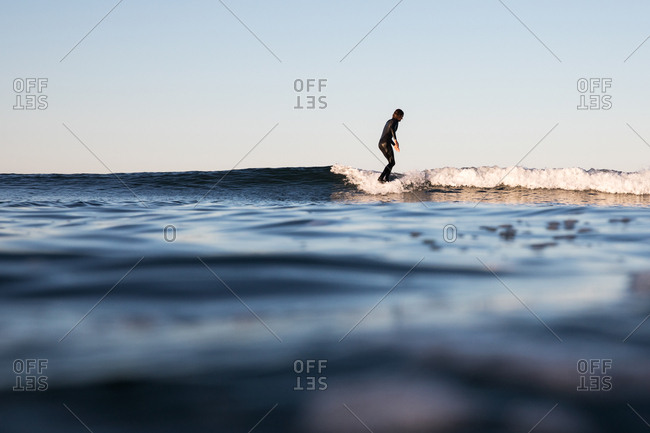October 3, 2017: Surfer riding a cresting ocean wave