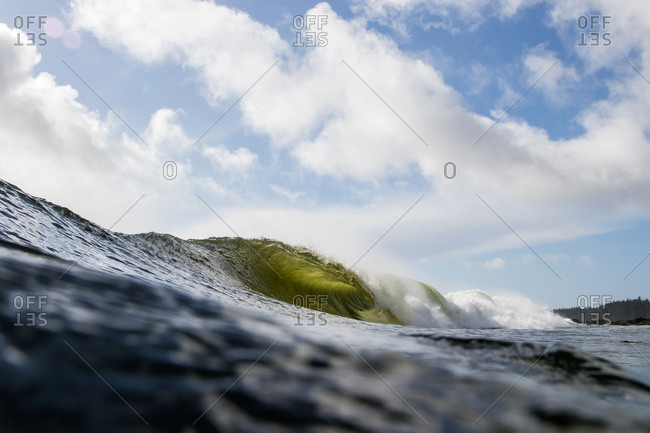 Curling swell under cloudy skies