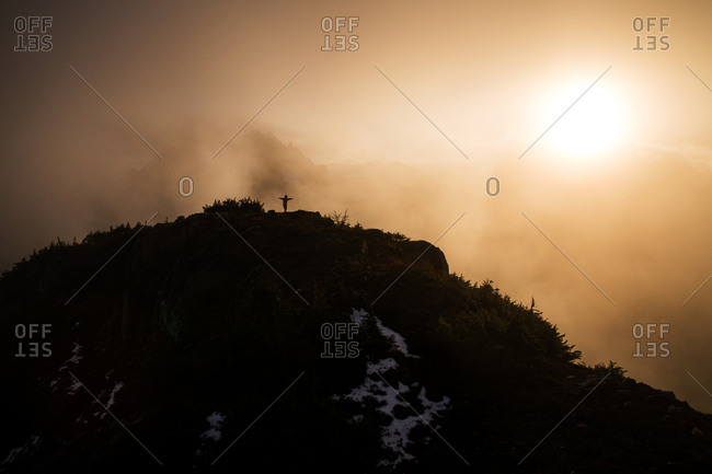 Silhouette of a person standing with their arms spread on a mountain