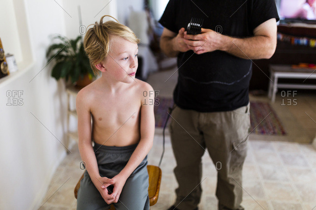 Man using clippers to give boy a haircut