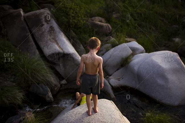 Two kids climbing on boulders