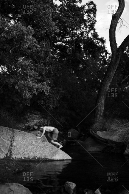 Boy climbing on lakeside boulder in black and white