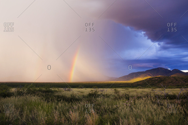Stormy clouds and rainbows over rural field and mountains