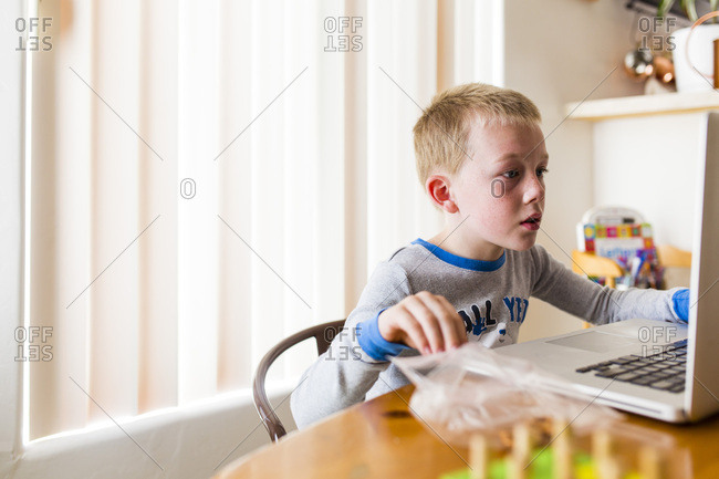 Blonde boy using laptop and eating a snack