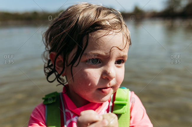Portrait of a little girl with wet hair standing near lake