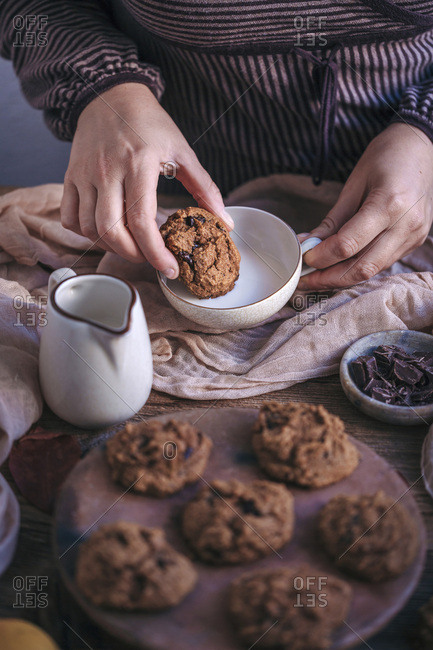Woman eating pumpkin chocolate chip cookies with a cup of milk