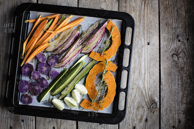 Chopped raw vegetables on baking sheet before roasting. Top view. Food background